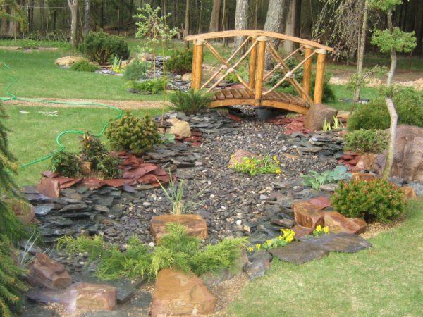 Ручей из камня с деревянным мостом в ландшафтном дизайне