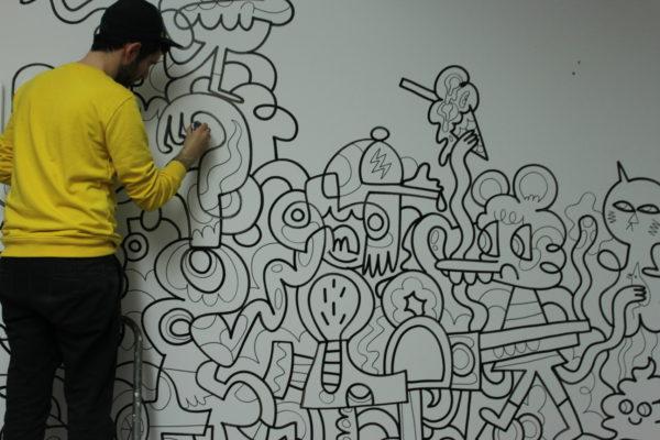 Мужчина рисует на стене