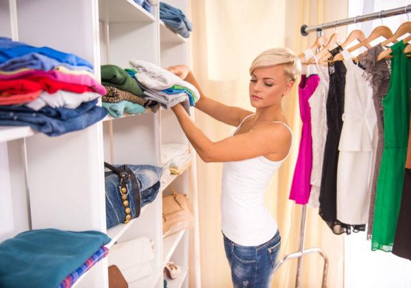 Девушка складывает одежду в шкаф