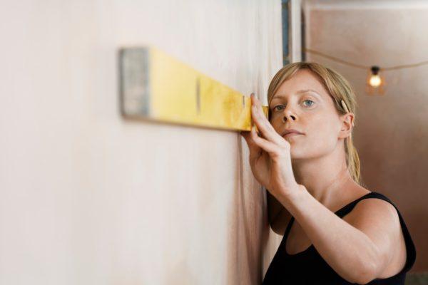 Девушка измеряет длину стены