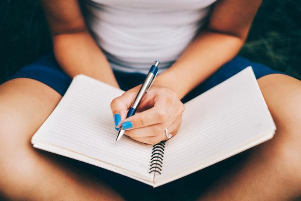 Девушка держит тетрадь и ручку