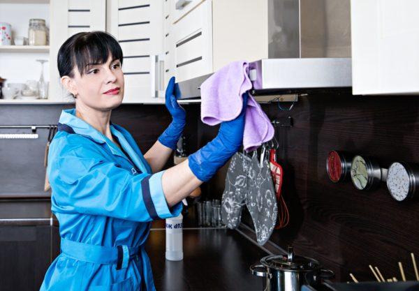 женщина протирает кухню