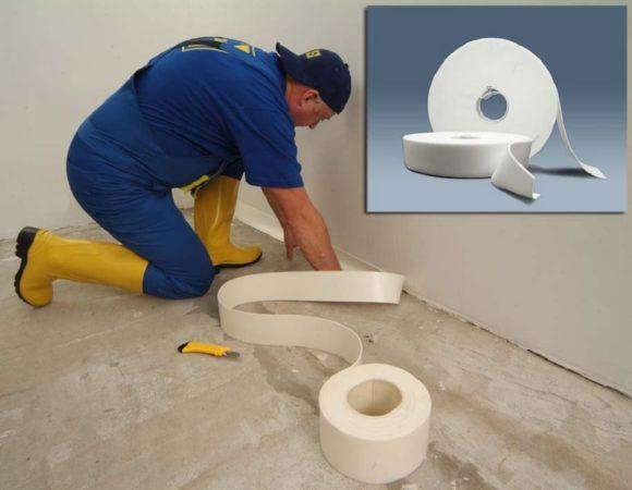 Рабочий закрепляет демпферную ленту на стене